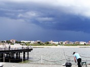 Fishing in stormy skies at Clacton Pier