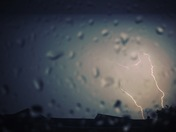 Lightning Strikes Through A Rain-Soaked Window