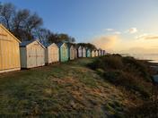 Colourful beach huts at dawn