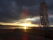 "Sunset shining on the sea, with the ""Exmouth Observation Wheel"" still lit up."