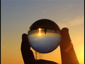 Sunset was photographed through a Sphere refraction of light house and water