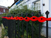 HAND MADE POPPIES ON THE RAILINGS NEAR THE WAR MEMORIAL