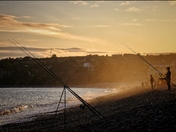 Fisherman enjoying an evening at the beach, whilst the sun goes down.